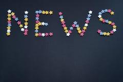 Het woordnieuws wordt geschreven door dun type van de sterren van het suikergebakje op een zwarte achtergrond, voor handel, verko royalty-vrije stock afbeeldingen