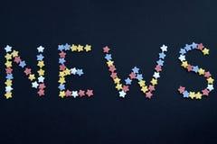 Het woordnieuws wordt geschreven in dun type van de sterren van het suikergebakje op een zwarte achtergrond, voor reclame, handel stock fotografie