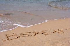 Het woordstrand in zand wordt geschreven dat Stock Fotografie