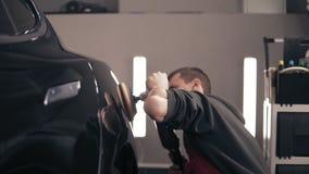 Het wrijven van zwarte auto om perfecte blik met een oppoetsende mashine te bereiken Jonge mannelijke represantative autocenter stock videobeelden