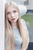 Het zachte portret van een mooi leuk meisje met lang blond haar met volledige lippen en blauwe ogen in een grijs kostuum, bekijkt Stock Foto's