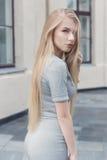 Het zachte portret van een mooi leuk meisje met lang blond haar met volledige lippen en blauwe ogen in een grijs kostuum, bekijkt Stock Afbeeldingen
