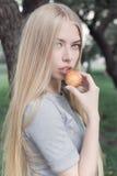 Het zachte portret van een mooi leuk meisje met lang blond haar met volledige lippen en blauwe ogen met in hand appel, bekijkt de Stock Foto's