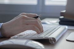 Het zakenlui overhandigt het werken met computer aan bureaudesktop stock afbeelding
