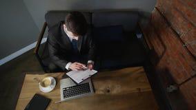 Het zakenmanwerk aangaande laptop en tekens omhoog de documenten in de koffie Hoogste mening stock footage