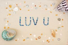Het zand op het strand in de zomer, de inschrijving houdt van u van shells op het zand Vlak leg Hoogste mening stock afbeeldingen