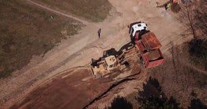 Het zand van de graafwerktuiglading in een vrachtwagen met luchtfotografiehommel stock footage