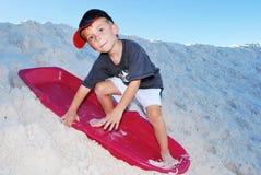 Het zand van de jongen het sledding Stock Afbeeldingen