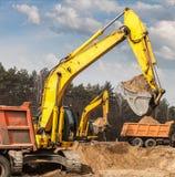 Het zand van het graafwerktuigenschip in vrachtwagens bij de wegenbouw royalty-vrije stock afbeeldingen