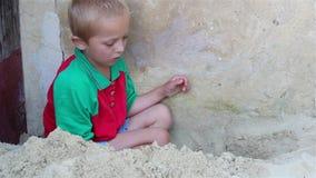 Het zand van jongensspelen stock video