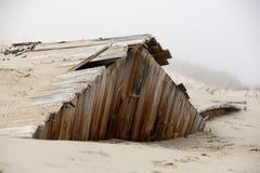 Het zand wint een gebouw in één van de oude mijnbouwsteden van terug de Skeletkust stock afbeelding
