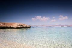 Het zandige strand met kalme duidelijke overzees, diep blauw hemel en deel van t Royalty-vrije Stock Fotografie