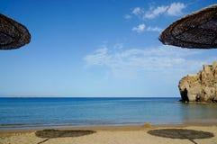 Het zandige strand van onder zon-wattled paraplu's stock fotografie
