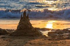 Het zandkasteel is in zonsondergang Het zonnespoor is in het zand Achtergrond stock foto