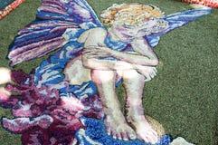 Het zandwerk die een engel met vlindervleugels tonen Stock Afbeelding