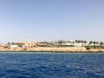 Het zeegezicht van de verre mooie bruine steenbergen en de diverse gebouwen op de kust en het blauwe zoute azuurblauwe overzees,  stock fotografie