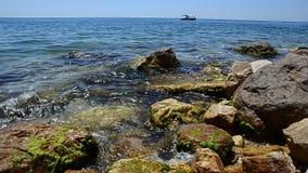 Het zeegezicht van de zomer Rotsachtig strand van azuurblauw water van oceaan of overzees Op de achtergrond een plezierbootzeilen stock video