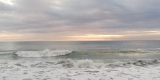 Het zeegezicht van de zonsondergang De zononderbrekingen door de lage zware wolken stock afbeelding
