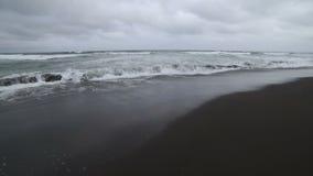 Het Zeegezicht van Kamchatka: mening van het strand van vulkanisch zand in Vreedzame Oceaan op de achtergrond van bergen en vulka stock video