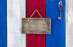 Het zeer belangrijke hangen door leeg teken op kleurrijke houten deur royalty-vrije stock afbeeldingen