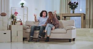 Het zeer gelukkige en charismatische paar in een nieuw huis bewoog zij die de grote dozen dragen in de woonkamer de zitting stock footage