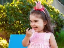 Het zeer gelukkige meisje die van de babypeuter, die gummies het lachen eten en in openluchtpartij glimlachen kleedde zich in roz stock fotografie
