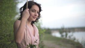 Het zeer mooie glimlachende meisje in lichtrose kleding ontspant op de schommeling bij het meerstrand stock footage