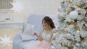 Het zeer mooie meisje drinkt champagne en zit op de bank in het decor van het Nieuwjaar stock footage