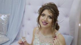 Het zeer mooie meisje drinkt champagne en zit op de bank in het decor van het Nieuwjaar stock videobeelden