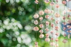 Het zeeschelpen mobiles gordijn met kleurrijk en de groene achtergrond stock foto