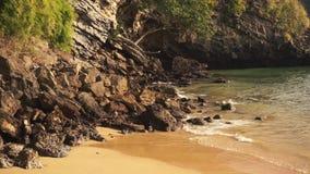 Het zeewater wast de stenen op het zandige strand stock videobeelden
