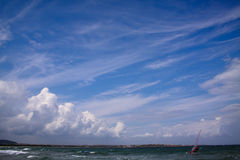 Het zeil van Windsurf op het overzees tegen blauwe hemel. Stock Foto