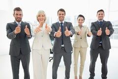Het zekere commerciële team gesturing beduimelt omhoog Royalty-vrije Stock Afbeeldingen
