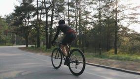 Het zekere geconcentreerde fietser pedaling op fiets in het park Weg het cirkelen opleiding Het cirkelen concept Langzame Motie stock video