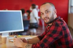 Het zekere mannelijke ontwerper texting op een mobiele telefoon in rode creatieve bureauruimte Royalty-vrije Stock Afbeeldingen