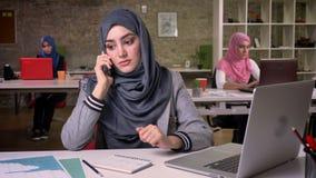 Het zekere ongebruikelijke moslimmeisje in hijab heeft ernstige bespreking over telefoon terwijl het zitten, moderne vibes, Arabi stock videobeelden