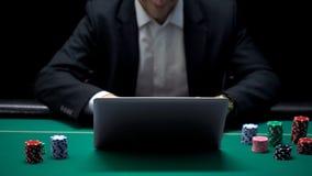Het zekere online gokker plaatsen wedt op laptop, kans om groot, succes te winnen stock afbeeldingen