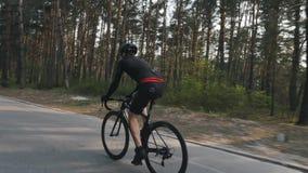 Het zekere sterke triathlete pedaling op fiets in het park als park van zijn opleidingsprogramma voor een ras Triatlonconcept stock video