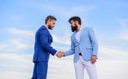 Het zekere teken zou u op partner moeten vertrouwen Mensen formele kostuums die achtergrond van de handen de blauwe hemel schudde stock foto