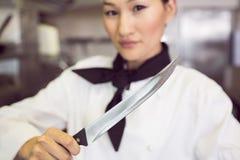 Het zekere vrouwelijke mes van de kokholding in keuken Stock Afbeeldingen