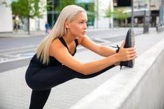 Het zekere Vrouwelijke Traliewerk van Atletenstretching leg on bij Stoep stock afbeeldingen