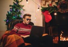 Het zelf-verzekerde mannetje maakt een aankoop op Internet via laptop met zonnebril stock afbeeldingen