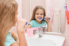 Het zes éénjarigenmeisje die de voortanden borstelen kijkt in de spiegel in de badkamers Stock Foto's