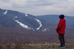 Het zes-jaar-oude kind in warme kleren in de volledige groei bevindt zich op de achtergrond van hooggebergte, mistig de lenteland stock fotografie