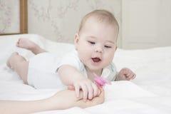 Het zes-maand-oude babymeisje ligt op haar maag en trekt haar hand aan het uitsteeksel Een klein kind in wit bekijkt de fopspeen royalty-vrije stock afbeelding