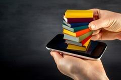 Het zetten of download kleurrijke boeken aan de slimme telefoon met plaats stock fotografie