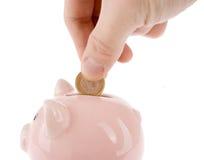 Het zetten van één euro muntstuk in spaarvarken Stock Foto