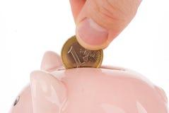 Het zetten van één euro muntstuk in spaarvarken Stock Afbeeldingen