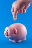 Het zetten van een muntstuk in een spaarvarken stock afbeelding