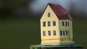 Het zetten van een stuk speelgoed huis op kleine stomp stock footage